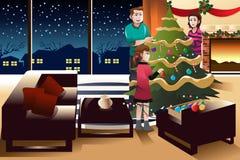Familia que adorna el árbol de navidad Imágenes de archivo libres de regalías