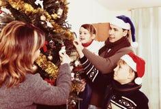 Familia que adorna el árbol de navidad Imagenes de archivo