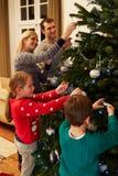 Familia que adorna el árbol de navidad en casa junto Imagen de archivo