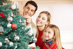 Familia que adorna el árbol de navidad en el país Fotos de archivo