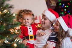 Familia que adorna el árbol de navidad en sala de estar Fotos de archivo libres de regalías