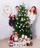 Familia que adorna el árbol de navidad en sala de estar imagen de archivo
