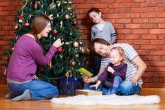 Familia que adorna el árbol de navidad Fotografía de archivo libre de regalías
