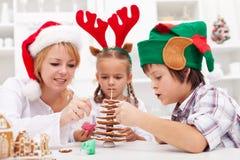 Familia que adorna el árbol de navidad del pan de jengibre Imágenes de archivo libres de regalías
