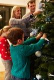 Familia que adorna el árbol de navidad en casa junto Foto de archivo