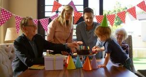 Familia que adorna la torta de cumpleaños en la sala de estar 4k almacen de video