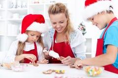 Familia que adorna las galletas de la Navidad Fotos de archivo