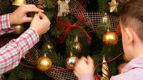 Familia que adorna un árbol de navidad junto almacen de metraje de vídeo