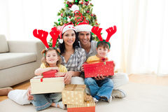 Familia que adorna un árbol de navidad Fotos de archivo