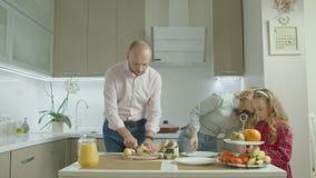Familia que aplica la mantequilla de cacahuete en tostada en cocina almacen de metraje de vídeo