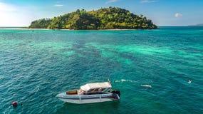 Familia que bucea cerca del barco en el mar tropical claro, la opini?n a?rea del abej?n desde arriba, la madre y los snorkelers d imagen de archivo