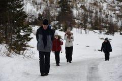 Familia que camina al aire libre en las montañas en el invierno de la nieve Imagenes de archivo