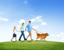 Familia que camina así como su perro casero al aire libre foto de archivo