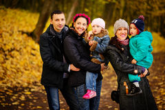 Familia que camina con dos niños en parque otoñal imagen de archivo