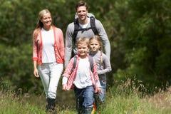 Familia que camina en campo imagen de archivo