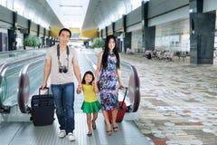 Familia que camina en el pasillo del aeropuerto Foto de archivo libre de regalías