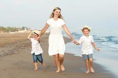 Familia que camina en la playa de la tarde durante puesta del sol Madre y dos hijos imagen de archivo