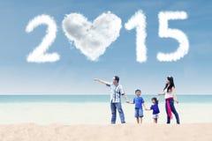 Familia que camina en la playa debajo de la nube de 2015 Foto de archivo libre de regalías