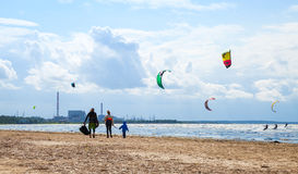 Familia que camina en la playa Paseo de Kitesurfers las ondas Fotos de archivo libres de regalías
