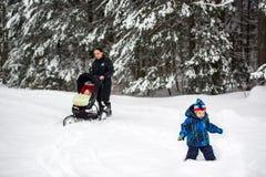 Familia que camina en nieve profunda en un parque Fotografía de archivo libre de regalías