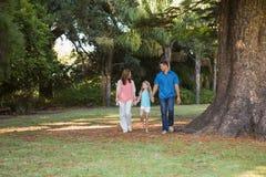 Familia que camina en un parque Fotos de archivo libres de regalías