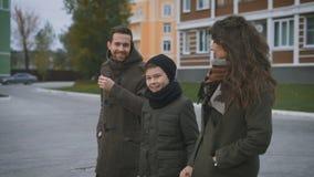 Familia que camina en un sendero El hombre en la capa gris escucha su esposa cuidadosamente Una mujer lleva a cabo una mano del ` almacen de metraje de vídeo