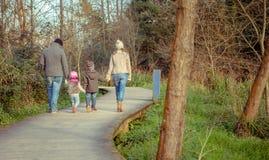 Familia que camina juntas llevando a cabo las manos en Imágenes de archivo libres de regalías