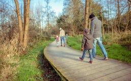 Familia que camina juntas llevando a cabo las manos en Fotos de archivo libres de regalías