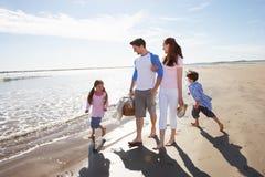 Familia que camina a lo largo de la playa con la cesta de la comida campestre Foto de archivo libre de regalías