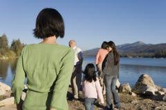 Familia que camina por la opinión de la parte posterior del lago Fotos de archivo