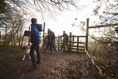 Familia que camina su paso del perro a través de una puerta en campo Imagenes de archivo