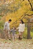 Familia que camina a través del parque en el otoño Imagenes de archivo