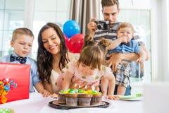 Familia que celebra el cumpleaños de la muchacha en casa Imagen de archivo libre de regalías