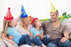 Familia que celebra el cumpleaños de los gemelos que se sienta en un sofá Foto de archivo libre de regalías