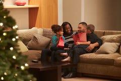 Familia que celebra la Navidad en casa vista de exterior Fotografía de archivo libre de regalías