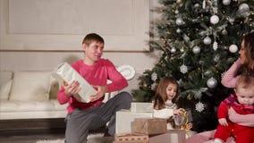 Familia que celebra la Navidad y que recibe presentes almacen de metraje de vídeo