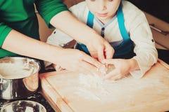 Familia que cocina a casa - las manos de la pasta de amasamiento de la madre y del hijo Foto de archivo