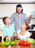 Familia que cocina el almuerzo Fotos de archivo