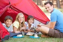 Familia que cocina el desayuno en acampada Foto de archivo libre de regalías