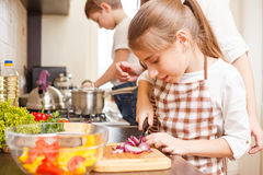 Familia que cocina el fondo Cebolla adolescente del corte de la muchacha Imágenes de archivo libres de regalías