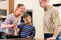 Familia que cocina en cocina Fotos de archivo