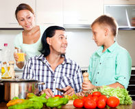Familia que cocina en la cocina Foto de archivo libre de regalías