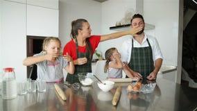 Familia que cocina junto Se divierten mucho que juega en cocina Hijas lindas con su jugar hermoso de los padres metrajes