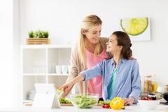 Familia que cocina la cena usando la PC de la tableta en la cocina Imagen de archivo