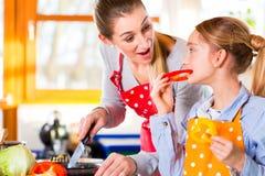 Familia que cocina la comida sana con la diversión Imagen de archivo libre de regalías