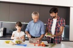 Familia que cocina la ensalada Un hombre, su padre y su hijo preparan una ensalada para la acción de gracias Fotografía de archivo libre de regalías