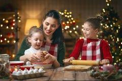 Familia que cocina las galletas de la Navidad imagen de archivo