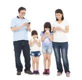 Familia que coloca una fila y que usa el teléfono elegante junto Imagen de archivo libre de regalías
