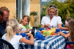 Familia que come café en el jardín Imagen de archivo