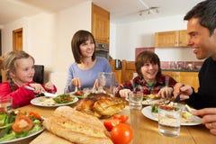 Familia que come el almuerzo junto en cocina Fotografía de archivo libre de regalías